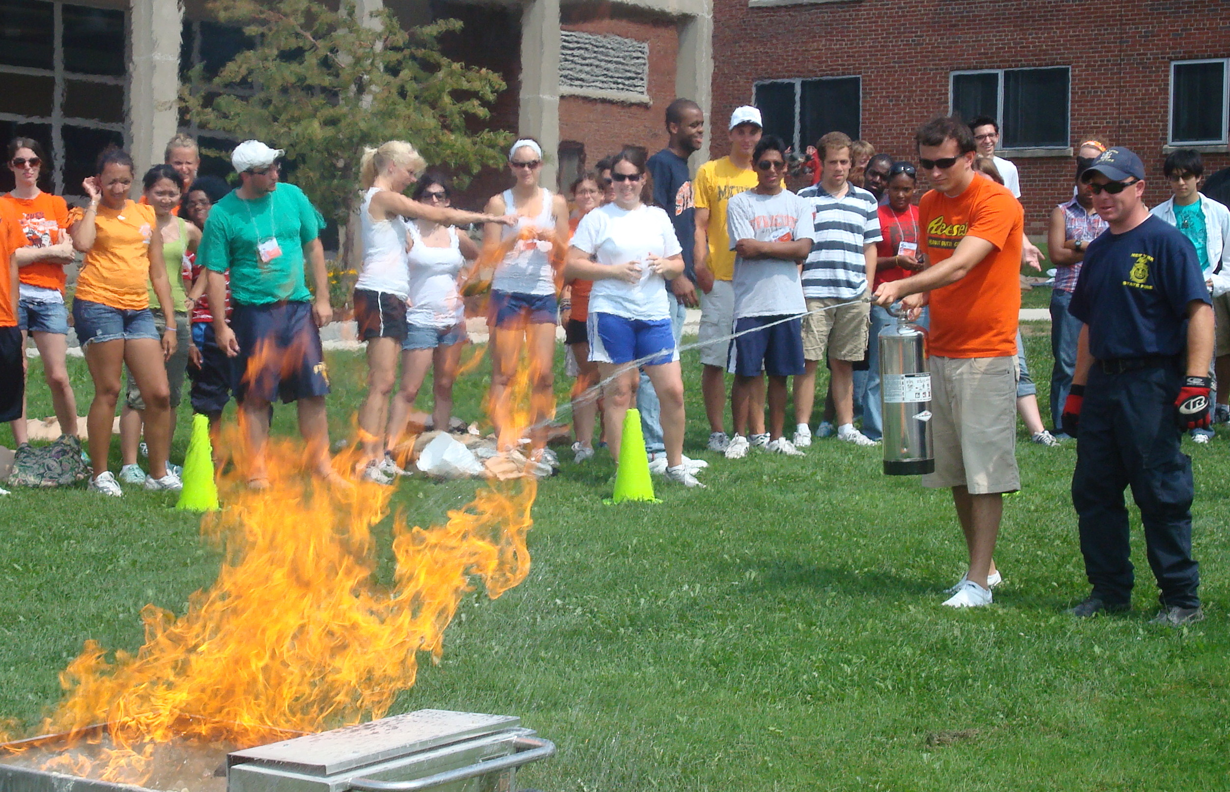 students gather around a grassy area outside day hall for fire safety training