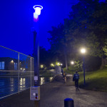 a blue light phone is illuminated at dusk near the tennis courts by the Women's Building