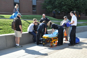 A group of people in uniform gather around a pregnant woman (actor) during an emergency drill, simulating a response to a potential emergency situation.